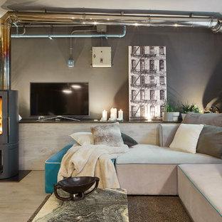 Foto de salón urbano con paredes grises, suelo de madera clara, televisor independiente y suelo beige