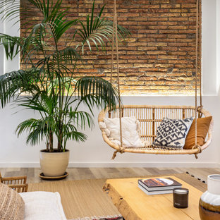 Inspiration for a tropical living room in Other with white walls, medium hardwood floors, brown floor and brick walls.