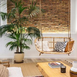 Immagine di un soggiorno tropicale con pareti bianche, pavimento in legno massello medio, pavimento marrone e pareti in mattoni