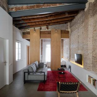 Ejemplo de salón abierto y ladrillo, industrial, de tamaño medio, ladrillo, sin chimenea, con televisor colgado en la pared, suelo gris, paredes blancas y ladrillo