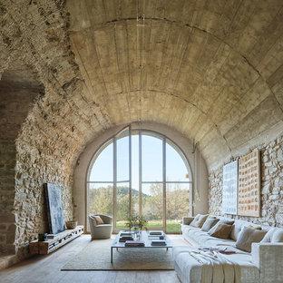 Modelo de salón para visitas mediterráneo con paredes beige, suelo de madera clara y suelo gris