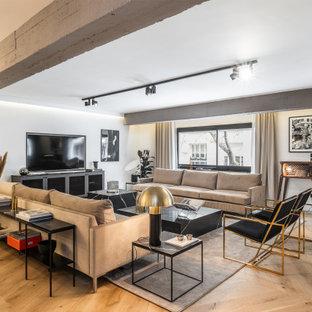 Diseño de salón abierto, escandinavo, con paredes grises, suelo de madera clara, televisor independiente y suelo beige