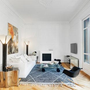 Ejemplo de salón cerrado, escandinavo, con paredes blancas, chimenea tradicional, marco de chimenea de yeso, televisor colgado en la pared, suelo de madera clara y suelo beige