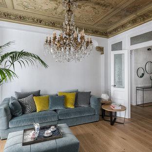 Modelo de salón ecléctico, grande, con suelo de madera clara y paredes blancas