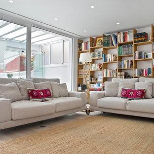 Imagen de biblioteca en casa contemporánea con paredes blancas, suelo de madera clara y suelo beige