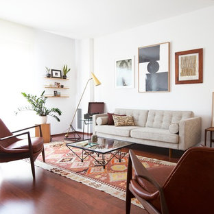 This is an example of a medium sized midcentury formal enclosed living room in Barcelona with white walls, medium hardwood flooring and no fireplace.