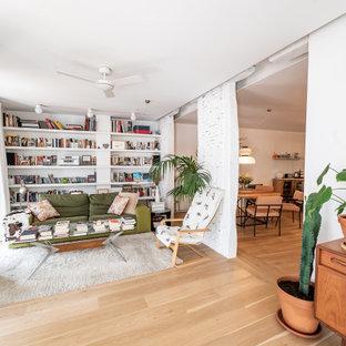 Imagen de salón cerrado, contemporáneo, con paredes blancas, suelo de madera clara, televisor independiente y suelo beige