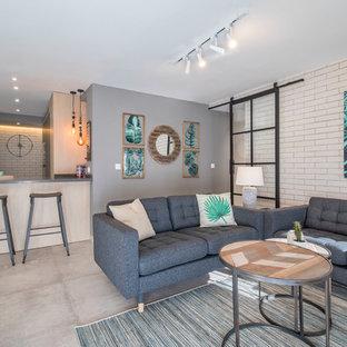 Modelo de salón abierto, actual, con paredes blancas, suelo de cemento y suelo gris
