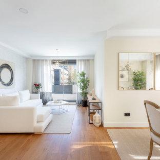 Ejemplo de salón abierto, actual, con paredes beige, suelo de madera en tonos medios y suelo marrón