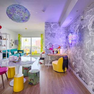 Idéer för att renovera ett mellanstort eklektiskt allrum med öppen planlösning, med mellanmörkt trägolv och grå väggar