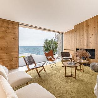 Imagen de salón abierto, costero, con paredes marrones, chimenea lineal, marco de chimenea de madera y suelo beige