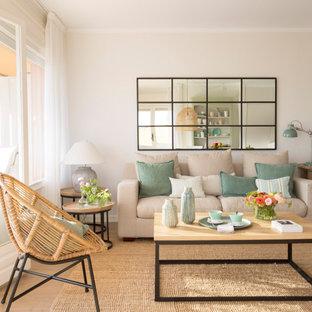 Modelo de salón abierto, costero, con paredes blancas, suelo de madera clara y suelo beige
