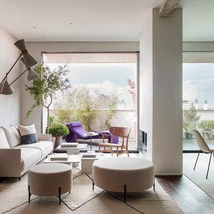 Diseño de salón abierto, actual, con paredes grises, suelo de madera oscura, chimenea de doble cara y suelo marrón