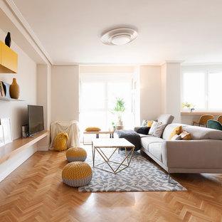 Imagen de salón cerrado, actual, de tamaño medio, con paredes blancas, televisor independiente, suelo de madera en tonos medios y suelo marrón