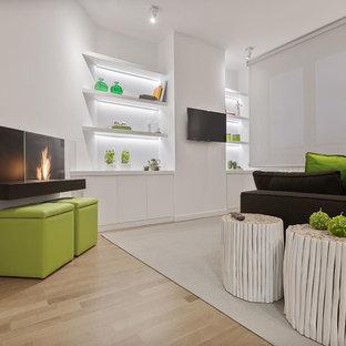 Diseño de biblioteca en casa abierta, moderna, pequeña, con paredes blancas, suelo de madera clara, chimenea lineal, marco de chimenea de metal, televisor colgado en la pared y suelo amarillo
