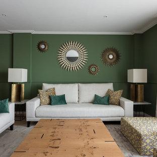 Foto de biblioteca en casa cerrada, clásica renovada, de tamaño medio, con paredes verdes, suelo de madera clara, chimeneas suspendidas, marco de chimenea de metal, televisor independiente y suelo beige