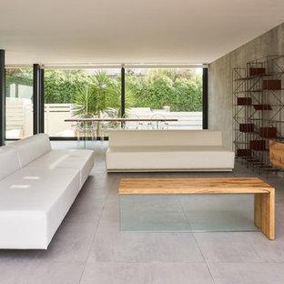 Imagen de salón abierto, actual, con paredes grises, televisor colgado en la pared y suelo gris