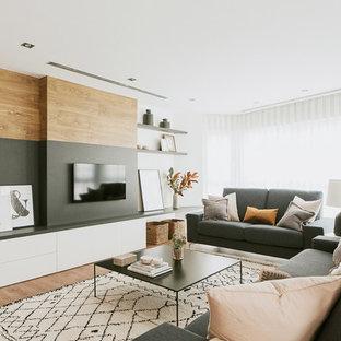 Ejemplo de salón contemporáneo con paredes blancas, suelo de madera en tonos medios, televisor colgado en la pared y suelo marrón