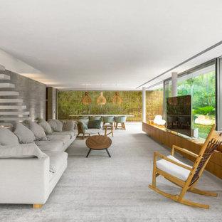 Foto de salón para visitas abierto, minimalista, extra grande, con paredes grises, televisor independiente, suelo gris y moqueta