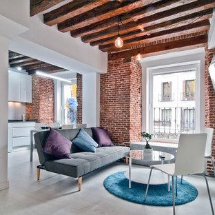 Modelo de salón abierto, industrial, pequeño, sin chimenea, con paredes blancas, suelo de madera clara, televisor colgado en la pared y suelo beige