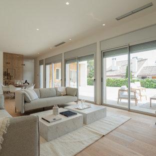 Diseño de salón abierto, contemporáneo, grande, sin televisor, con paredes blancas, suelo de madera clara y suelo beige