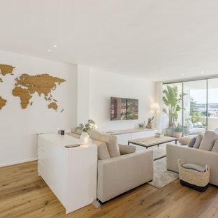 Modelo de salón abierto, actual, con paredes blancas, suelo de madera en tonos medios, televisor colgado en la pared y suelo marrón