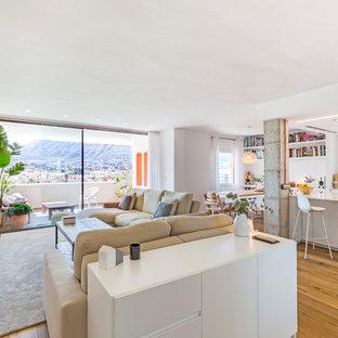 Imagen de salón abierto, actual, grande, con paredes blancas, suelo de madera en tonos medios, televisor colgado en la pared y suelo marrón