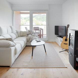 Foto de salón contemporáneo con paredes blancas, suelo de madera clara, televisor independiente y suelo beige