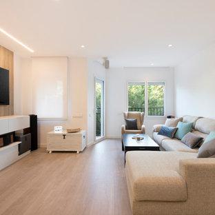Imagen de salón abierto, contemporáneo, de tamaño medio, sin chimenea, con paredes blancas, suelo laminado, televisor colgado en la pared y suelo beige
