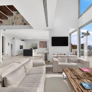 Ejemplo de salón contemporáneo, extra grande, con suelo de baldosas de porcelana, suelo beige, paredes blancas, chimenea de doble cara, marco de chimenea de yeso y televisor colgado en la pared