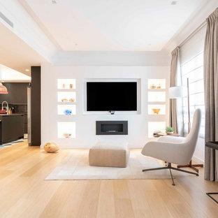 Imagen de salón con barra de bar abierto, contemporáneo, con paredes blancas, suelo de madera clara, chimenea lineal, televisor colgado en la pared y suelo beige
