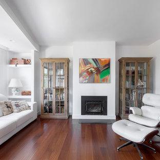 Imagen de salón para visitas cerrado, contemporáneo, con paredes blancas, suelo de madera oscura, chimenea tradicional, marco de chimenea de yeso, televisor colgado en la pared y suelo marrón