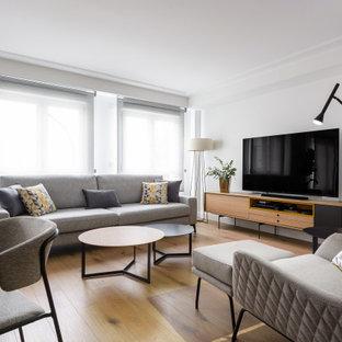 Diseño de salón abierto, contemporáneo, grande, sin chimenea, con suelo laminado, paredes blancas, televisor independiente y suelo marrón