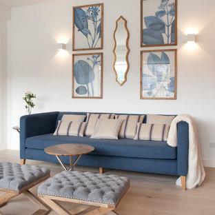 Ejemplo de biblioteca en casa abierta, marinera, grande, con paredes blancas, suelo de madera clara y suelo beige