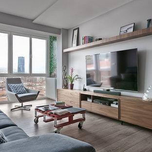 Imagen de salón para visitas cerrado, actual, de tamaño medio, sin chimenea, con paredes grises, suelo de madera oscura, televisor colgado en la pared y suelo gris