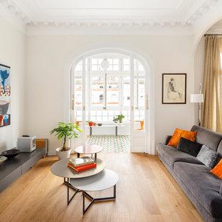 Ejemplo de salón para visitas abierto, actual, con paredes blancas, suelo de madera en tonos medios y suelo marrón