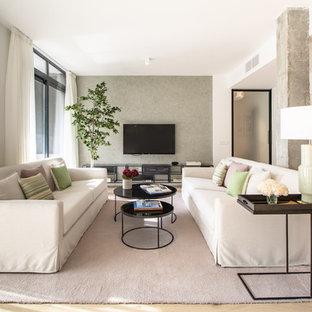 Foto de salón actual con paredes blancas, suelo de madera en tonos medios, televisor colgado en la pared y suelo marrón