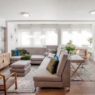 Diseño de salón abierto, actual, con paredes grises, suelo de madera en tonos medios y suelo marrón
