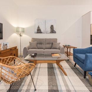 Modelo de salón para visitas abierto, contemporáneo, de tamaño medio, sin chimenea, con paredes blancas, suelo de madera clara y televisor colgado en la pared