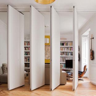 Ejemplo de biblioteca en casa cerrada, contemporánea, de tamaño medio, con paredes blancas y suelo de madera en tonos medios