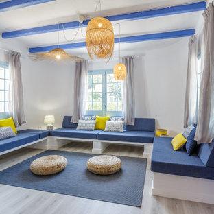 Diseño de salón para visitas cerrado, costero, con paredes blancas, suelo de madera clara, televisor colgado en la pared y suelo gris