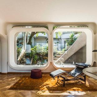 Ejemplo de salón actual con suelo de madera en tonos medios, paredes blancas y suelo marrón