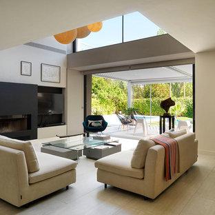 Diseño de salón abierto, minimalista, con paredes beige, chimenea lineal, televisor colgado en la pared y suelo beige