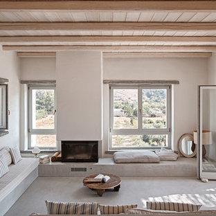 バルセロナの地中海スタイルのおしゃれな独立型リビング (白い壁、コンクリートの床、標準型暖炉、漆喰の暖炉まわり、テレビなし、グレーの床、フォーマル) の写真