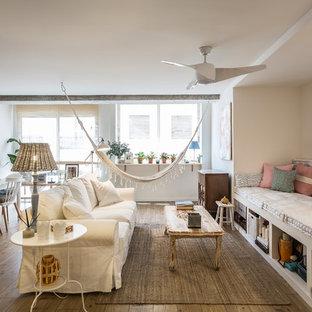 Ejemplo de salón abierto, ecléctico, grande, con paredes blancas, suelo laminado, televisor colgado en la pared y suelo marrón