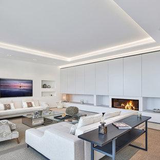 Foto de salón para visitas abierto, contemporáneo, grande, con paredes blancas, chimenea lineal, televisor colgado en la pared y suelo beige
