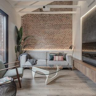Foto de salón abierto, urbano, de tamaño medio, con paredes multicolor, suelo laminado, televisor colgado en la pared y suelo marrón