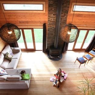 他の地域の広いラスティックスタイルのおしゃれなLDK (フォーマル、マルチカラーの壁、無垢フローリング、薪ストーブ、石材の暖炉まわり、マルチカラーの床) の写真