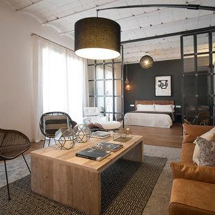 Modelo de salón para visitas abierto, urbano, con paredes blancas y suelo de madera en tonos medios