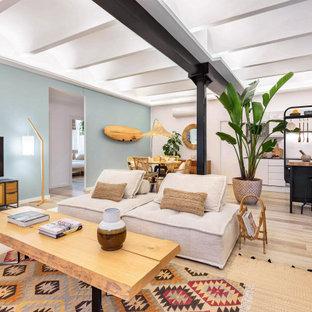 Ejemplo de salón abierto, exótico, sin chimenea, con paredes azules, suelo de madera clara, televisor independiente y suelo beige